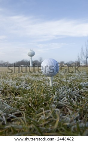 Elevated balls in perspective: golf ball teed up on frosty field with water tower on horizon