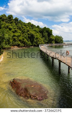 Elevated Boardwalk along Tropical Coastline. Walking Path through Paradise. Bright Sunny Day. Vertical Layout with Copy Space. - stock photo