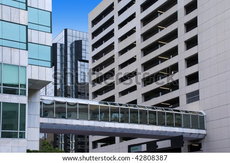 Elevated glass-covered city walkway between a tall office building and a tall parking garage. - stock photo