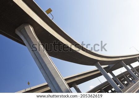 Elevated highway interchange structure, curved winding road under clear blue sky - stock photo
