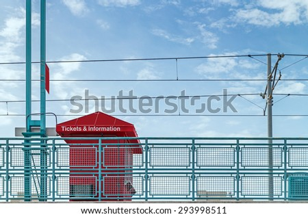Elevated light rail commuter train station ticket booth. Buy tickets and get information on train destination and schedule. Blue sky and clouds background.  - stock photo
