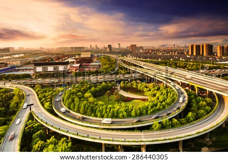 Elevated overpass with skyline of modern city during sunset. - stock photo
