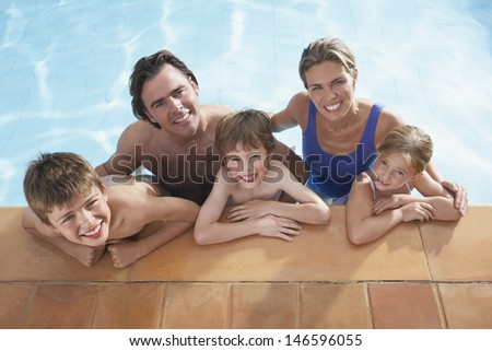 Elevated portrait of a happy couple with three children in swimming pool - stock photo