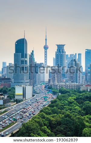 elevated road with shanghai skyline at dusk,modern city and traffic background.