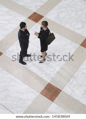 Elevated view of a businessman and woman talking on tiled floor - stock photo