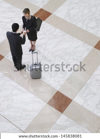 Elevated view of a businessman presenting business card to woman on tiled floor - stock photo