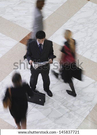 Elevated view of a businessman reading newspaper amongst blurred people walking on tiled floor - stock photo