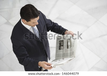 Elevated view of a businessman reading newspaper on tiled floor - stock photo