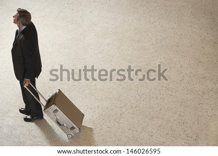 Elevated view of a businessman standing with suitcase in airport lobby - stock photo