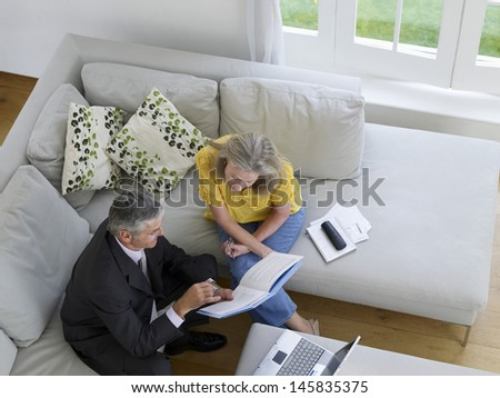 Elevated view of a mature woman sitting on sofa with financial advisor - stock photo