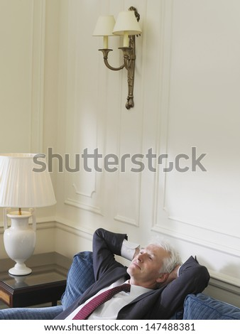 Elevated view of a serious middle aged businessman leaning back with hands behind head on sofa - stock photo