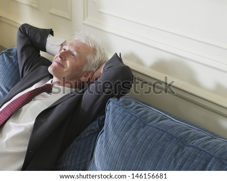 Elevated view of a smiling middle aged businessman leaning back with hands behind head on sofa - stock photo