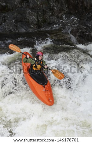 Elevated view of a woman kayaking in rough river - stock photo