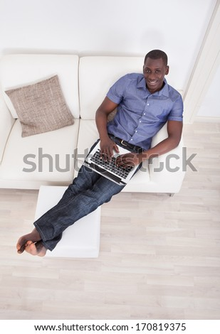 Elevated View Of African Man Sitting On Couch With Laptop - stock photo