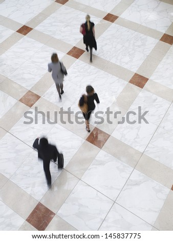 Elevated view of blurred business people walking on tiled floor - stock photo
