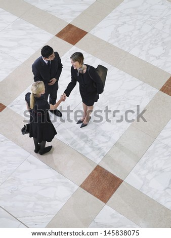 Elevated view of business people shaking hands on tiled floor - stock photo
