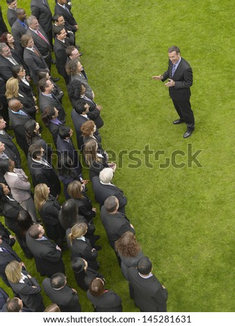 Elevated view of businessman facing large group of business people - stock photo