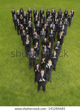 Elevated view of large group of business people clapping in triangle formation - stock photo