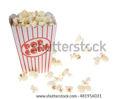Elevated view of popcorn in tub and scattered on white surface