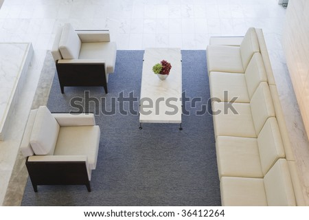 Elevated view of red flowers in a vase on coffee table in a modern lobby.