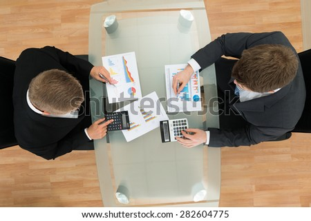Elevated View Of Two Businessman With Pen And Calculator Analyzing Graph - stock photo