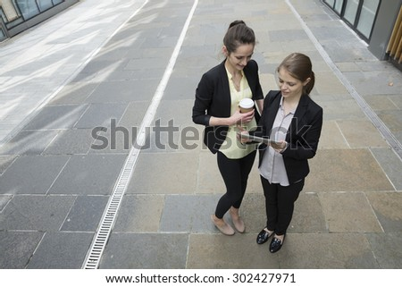 Elevated view of two Caucasian Business women using digital tablet computer. - stock photo