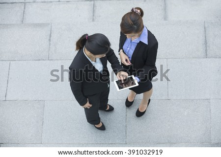 Elevated view of two Chinese Business women using digital tablet computer. - stock photo