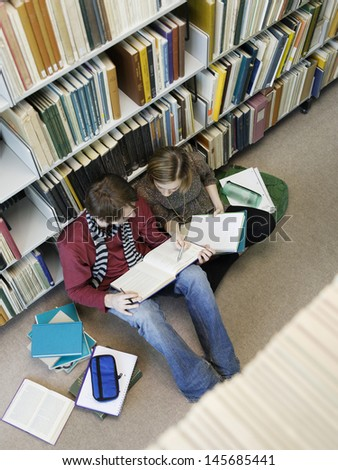 Elevated view of two students siting on floor and doing homework in library  - stock photo