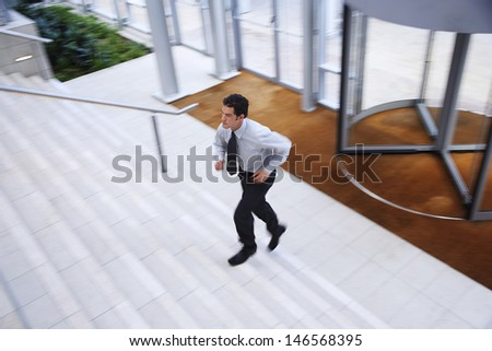 Elevated view of young businessman running upstairs in office lobby - stock photo