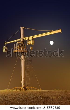 Elevating crane on a moonlit night under floodlights. - stock photo