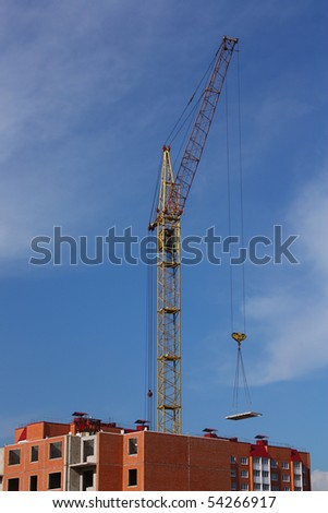 Elevating cranes on building against blue sky - stock photo