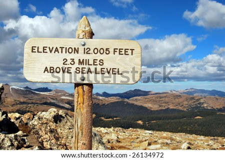 Elevation 12,005 Feet, 2.3 Miles Above Sea Level sign at the top of Rocky Mountain National Park in Colorado