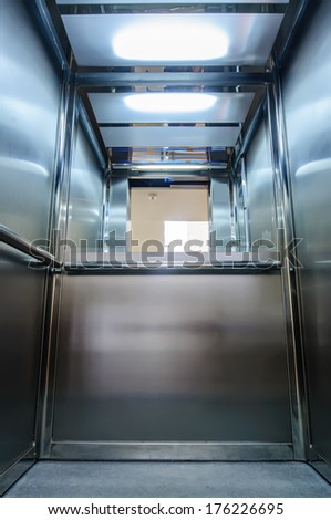 Elevator interior with mirror, alloy and open door