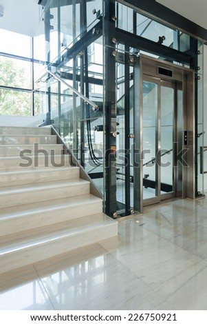 Elevator next to staircase in business centre - stock photo