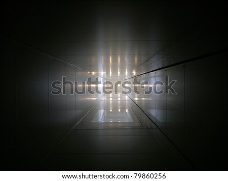 Elevator tube with light spots at the end of it - stock photo