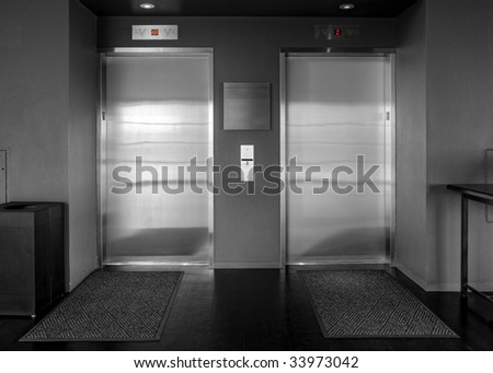 Elevators in black & white with red numbers above the doors