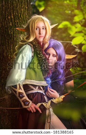 Elf boy and elf girl stayng near the tree - stock photo