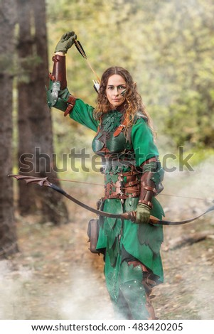 Elf woman in green leather armor with the bow and arrows is hunting on the forest background.