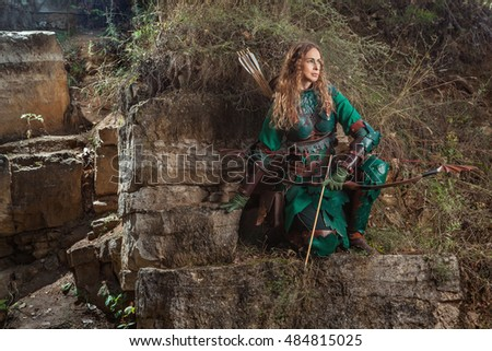 Elf woman in green leather armor with the bow and arrows is hunting on the rocks background.