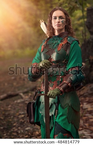 Elf woman in green leather armor with the sword on the forest background.