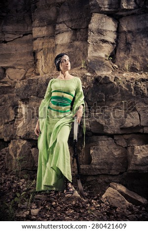 Elf woman with the magic bow on the rocks background. - stock photo
