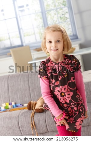 Elfish-looking little girl posing at home in living room, smiling. - stock photo