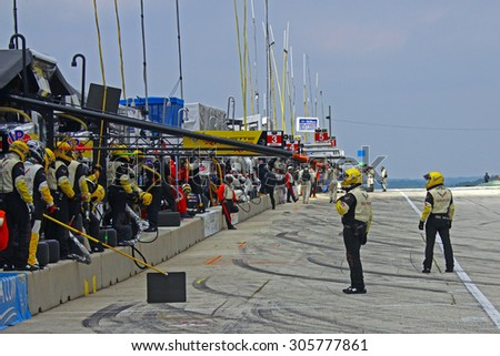 Elkhart Lake, Wisconsin USA - August 9, 2015: Road America road course, IMSA. Pit crews for Corvette racing cars, wait in pit lane, before refuelling and tire change. - stock photo