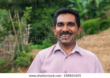 ELLA, SRI LANKA - MARCH 2, 2014: Portrait of local farmer posing on tea plantation. Ella is famous for the tea plantations and stunning views across the countryside. - stock photo