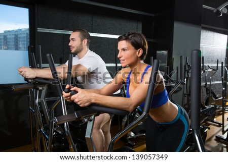elliptical walker trainer man and woman at black gym training aerobics exercise - stock photo