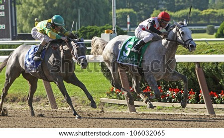 "ELMONT, NY - JUN 23: Rajiv Maragh and ""Zo Impressive"" win The Grade 1 Mother Goose Stakes at Belmont Park on Jun 23, 2012 in Elmont, NY. - stock photo"