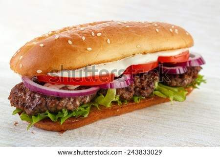 Elongated hamburger (burger sandwich) with three grilled patties , lettuce ,  red onion , tomato and mayonnaise - stock photo