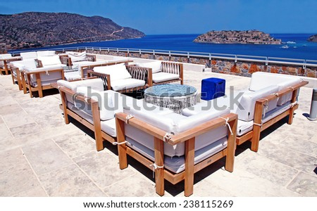 ELOUNDA, GREECE - JULY 13, 2012: Terrace sea view with outdoor lounge furniture in a luxury resort Elounda, Crete, Greece. - stock photo