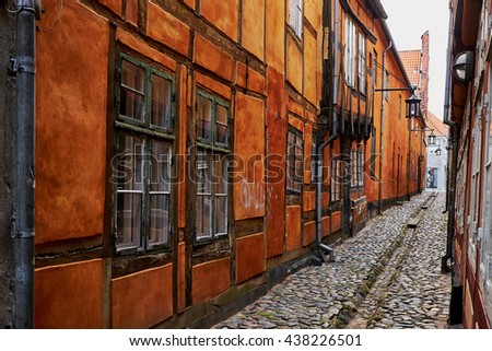ELSINORE, DENMARK - APRIL 30, 2016: Yellow timbered historic buildings surrounding  a narrow alley paved with cobblestones, in the medieval quarter of Elsinore. - stock photo
