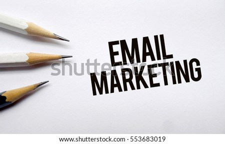 Email marketing  memo written on a white background with pencils